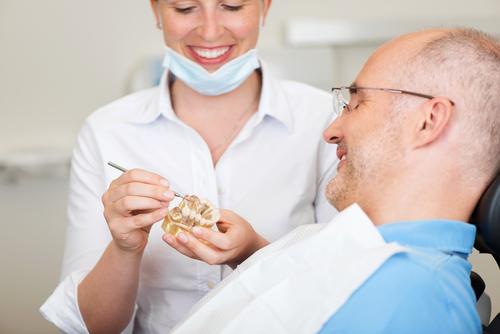Dentist explaining implants and bridges to man